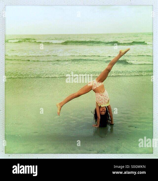 Girl doing a cartwheel on the beach - Stock Image