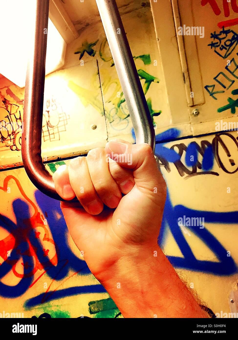 Man's hand holding pivoted grab handle on vintage New York City subway - Stock Image