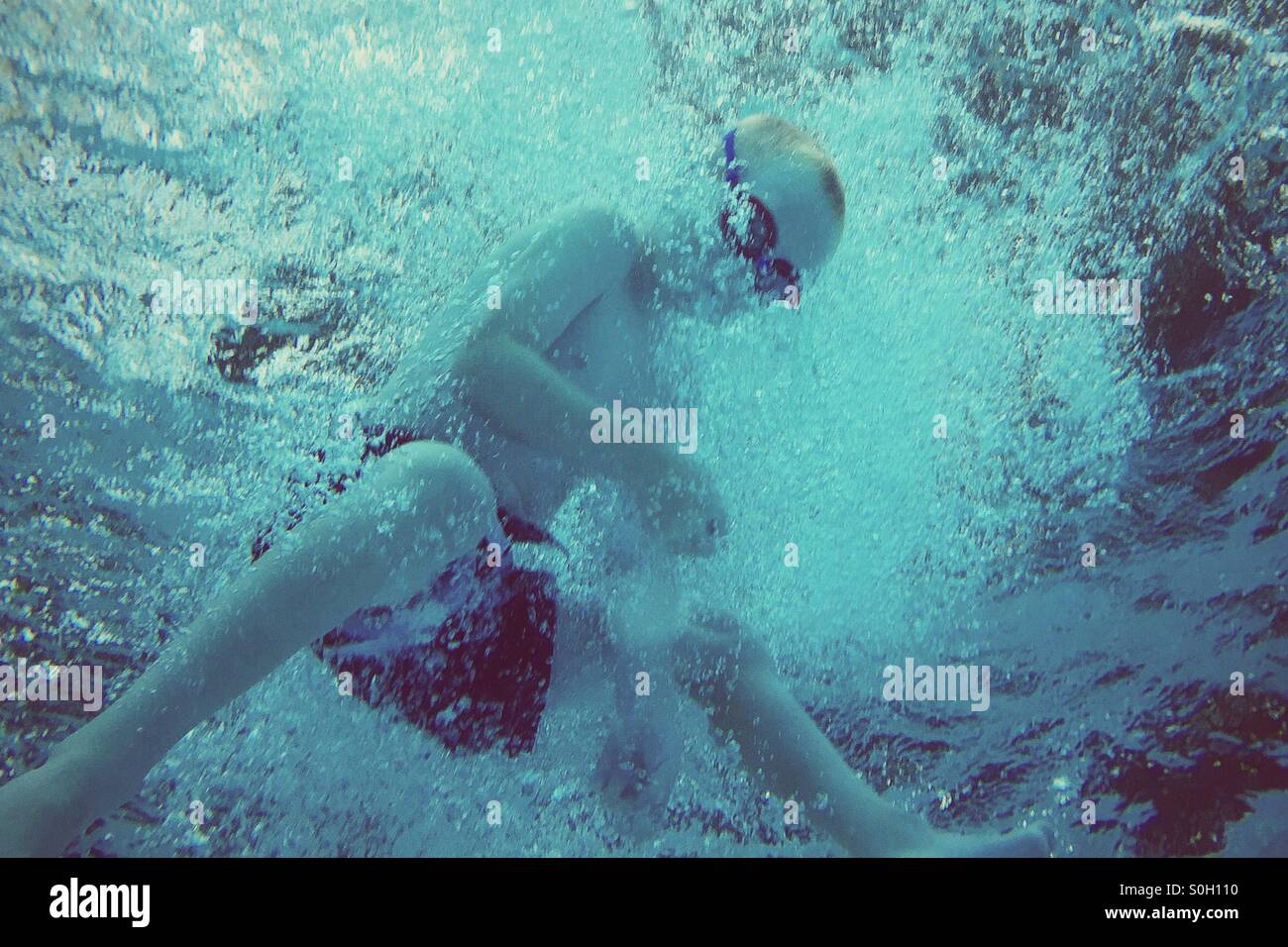 Dynamic underwater shot of a young boy diving into water, as seen from below. - Stock Image