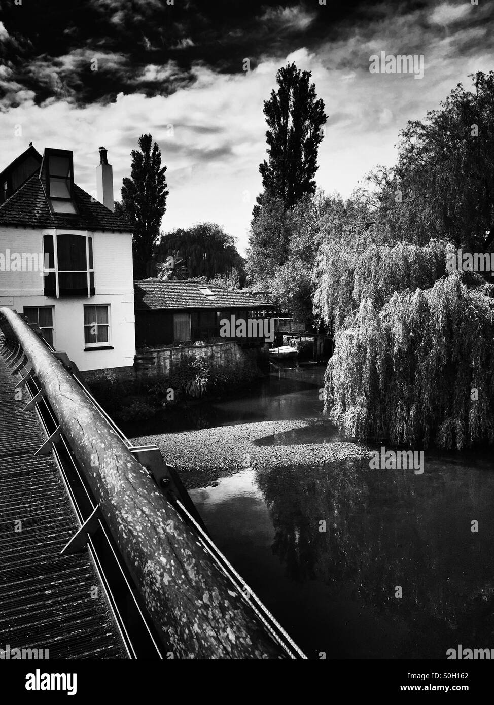 Riverside house near a picturesque bridge - black and white Stock Photo