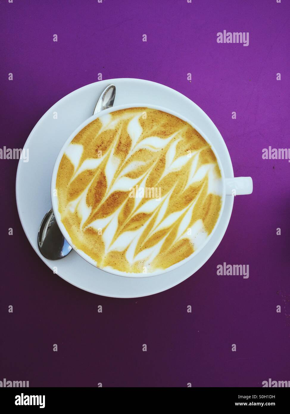 Top view of cup of coffee with  saucer and spoon on purple background. - Stock Image