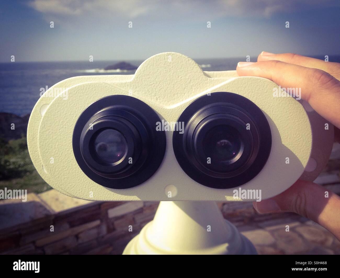 A tourist using a binocular - Stock Image