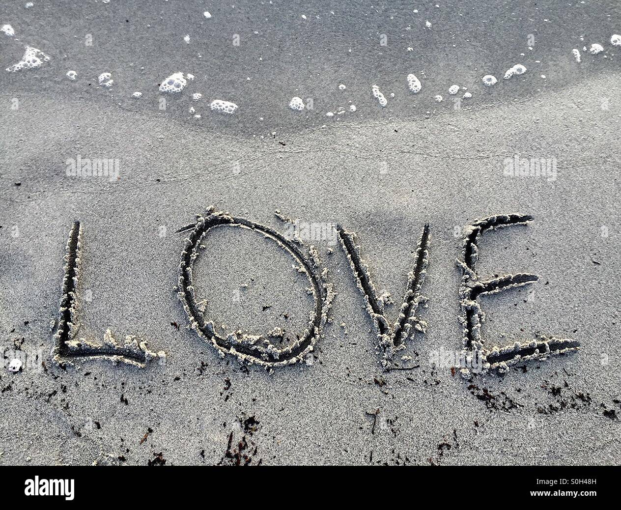 Love written in the sand Stock Photo