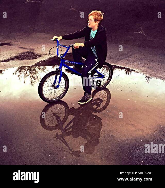 After a heavy rain storm a young BMX rider sits on his bike in a puddle reflecting his image. - Stock Image