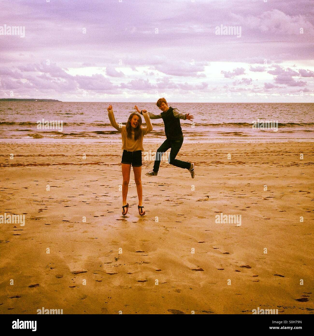 Boy and girl leaping on beach - Stock Image