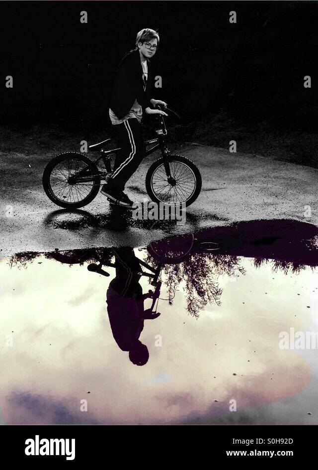Young person sitting next too a puddle on his BMX bike with the water reflecting his image, like a mirror - Stock Image