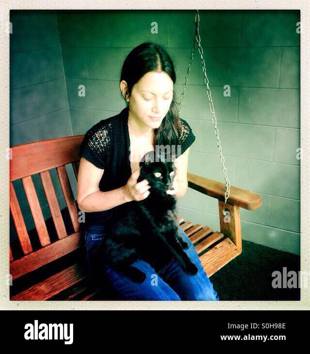 Woman petting black cat - Stock Image
