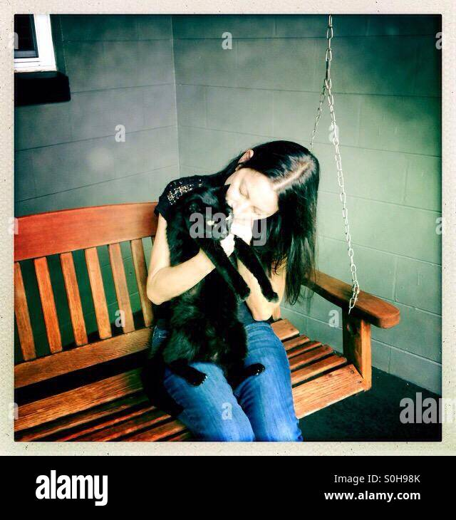 Woman hugging black cat - Stock Image
