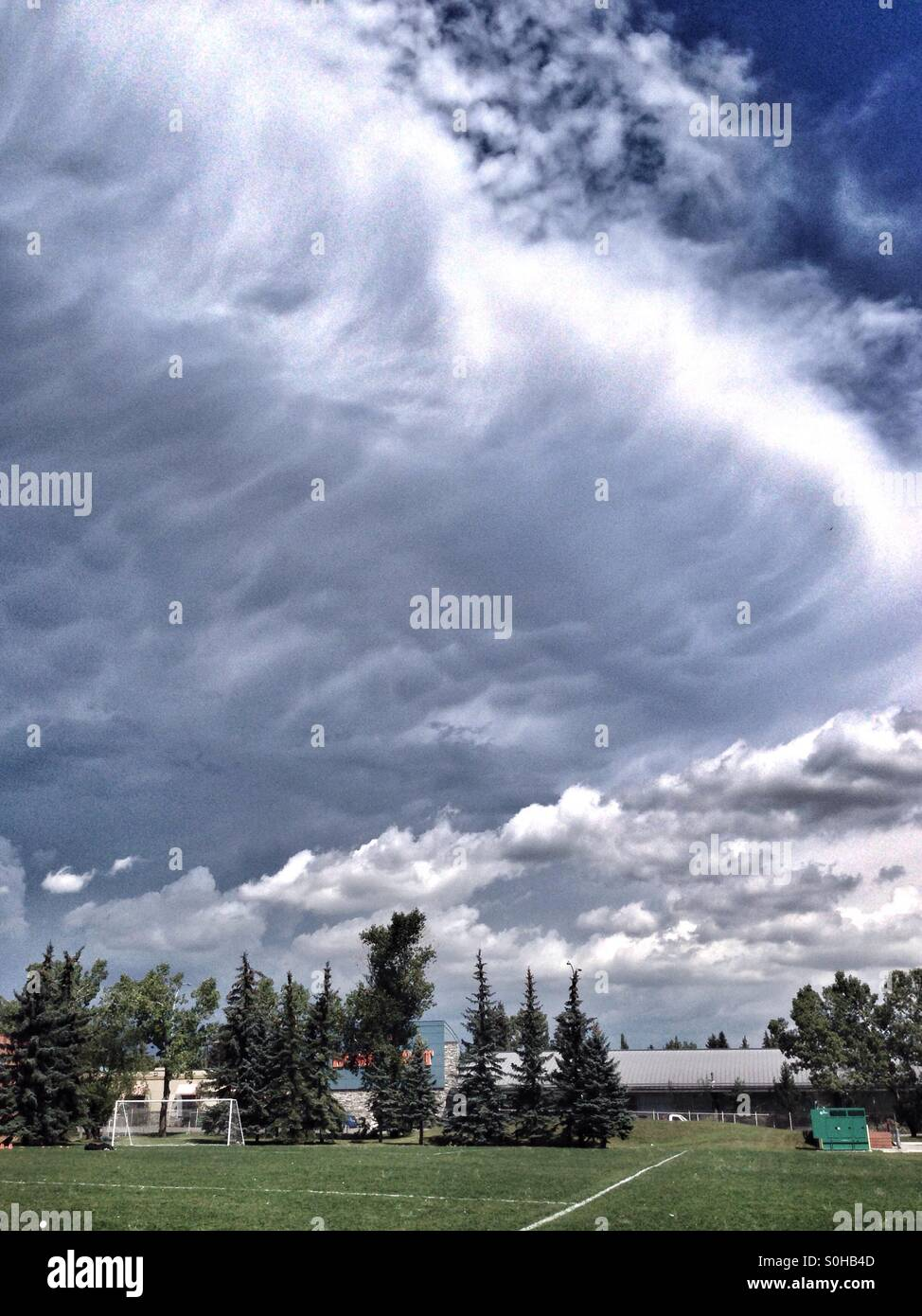 Large Cumulonimbus cloud approaching a sports field in Calgary, Alberta, Canada. July 2015. - Stock Image