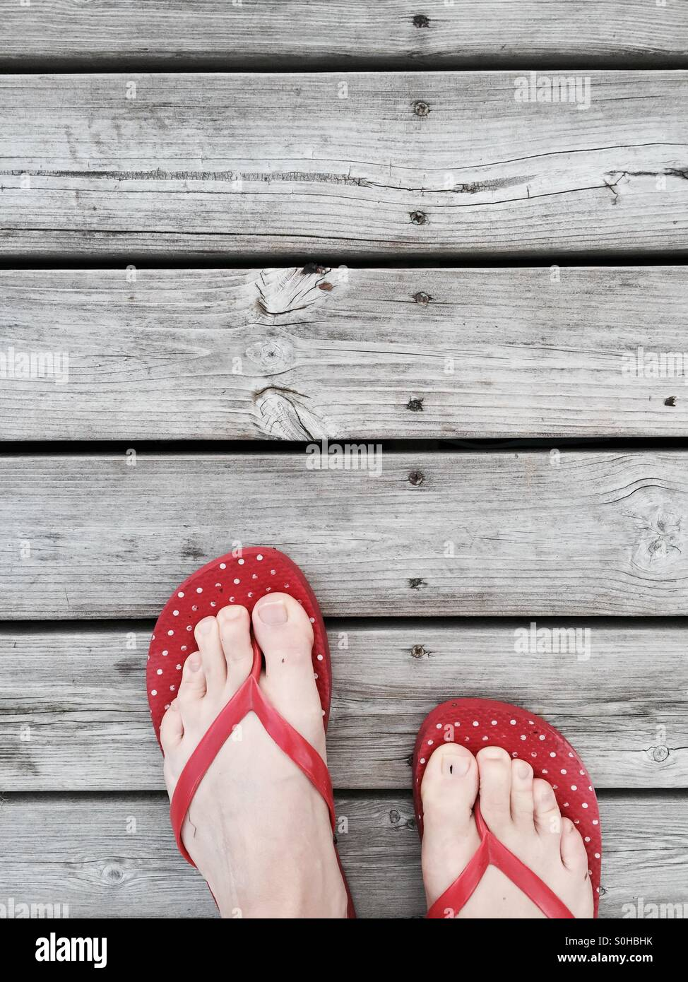 Red flip flops on a wooden wharf in summer cottage, Finland - Stock Image