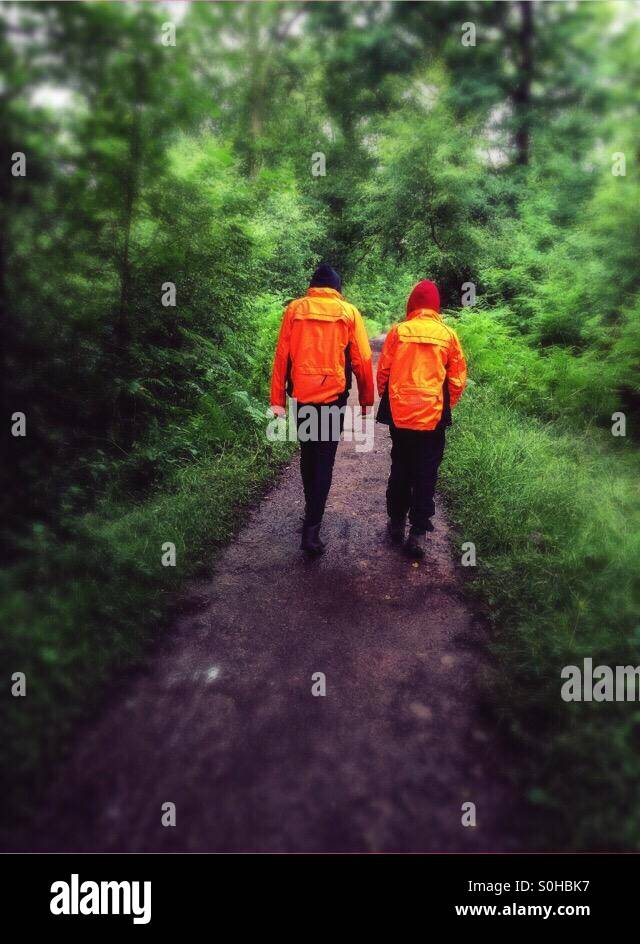 Two people walking through the woods with matching fluorescent orange coats on - Stock Image