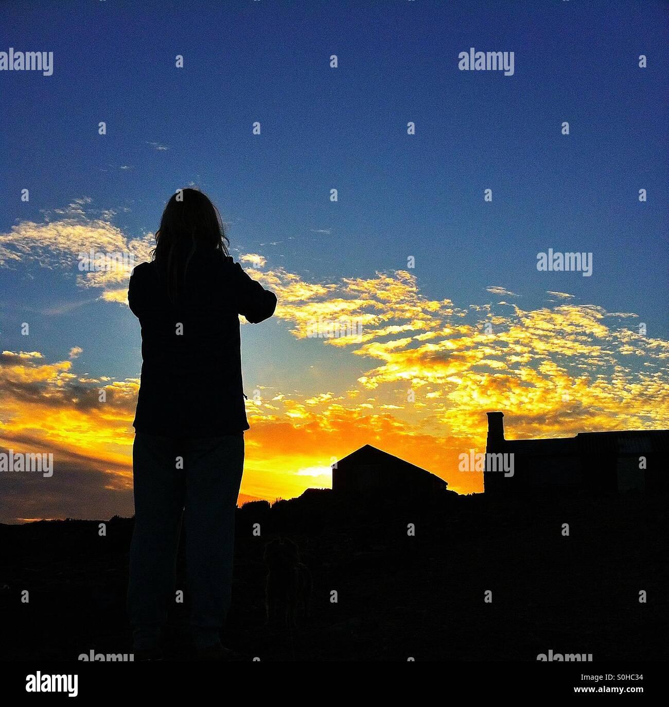 Watching the setting sun - Stock Image