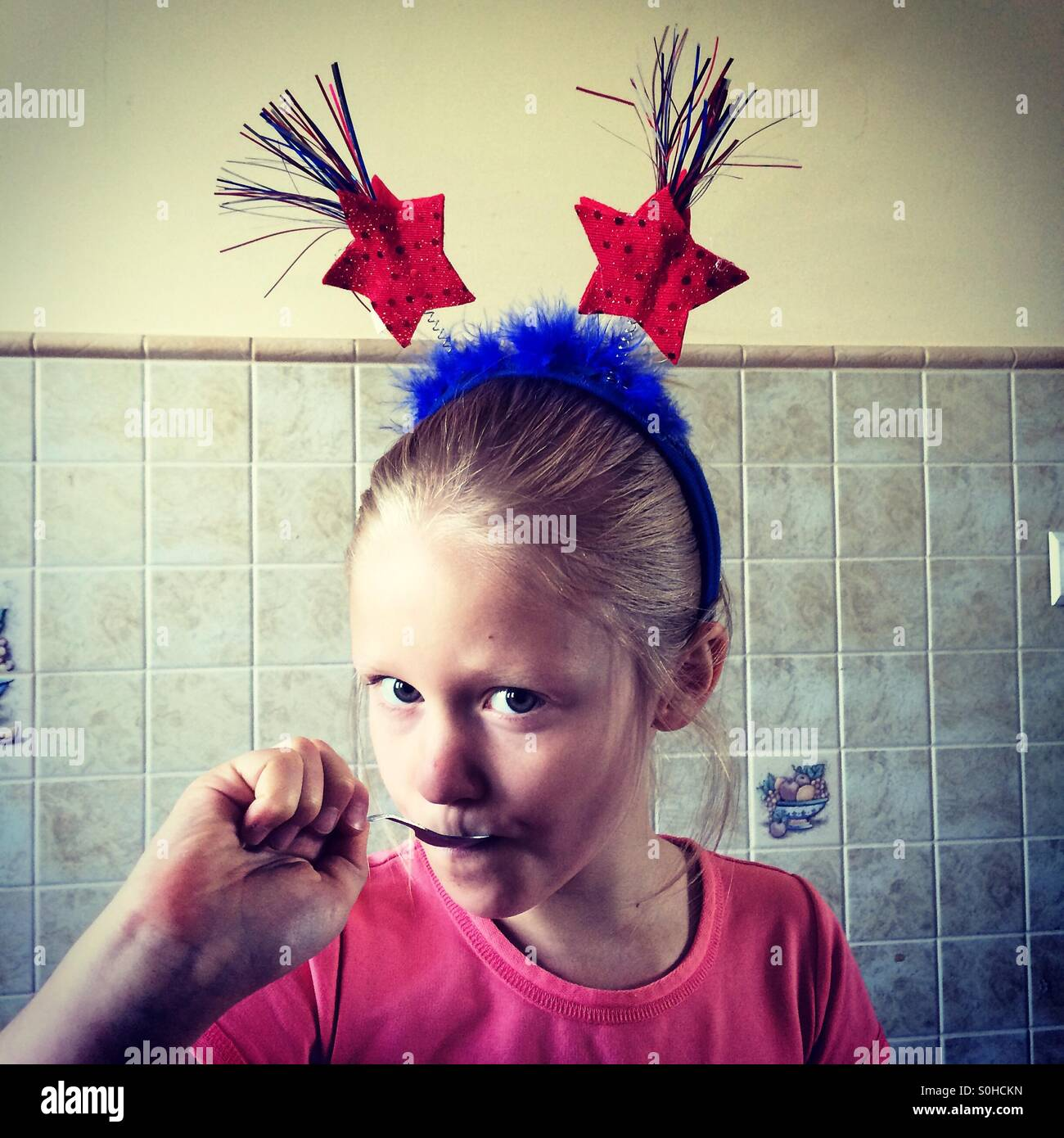 Pretty young girl with patriotic headband eating - Stock Image