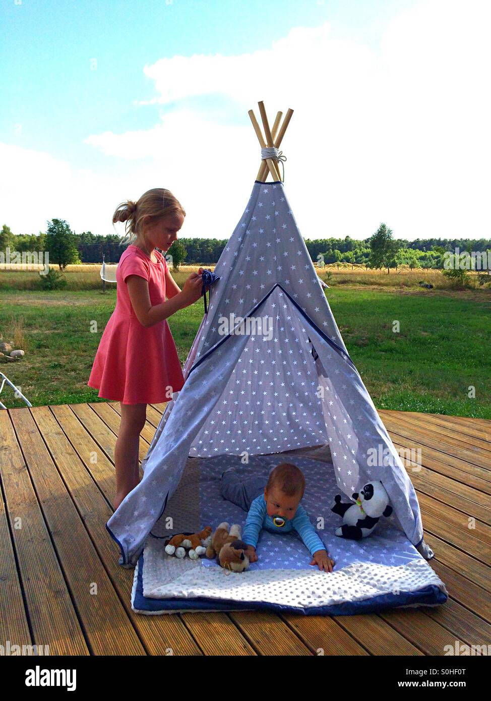 Siblings playing outside in teepee - Stock Image