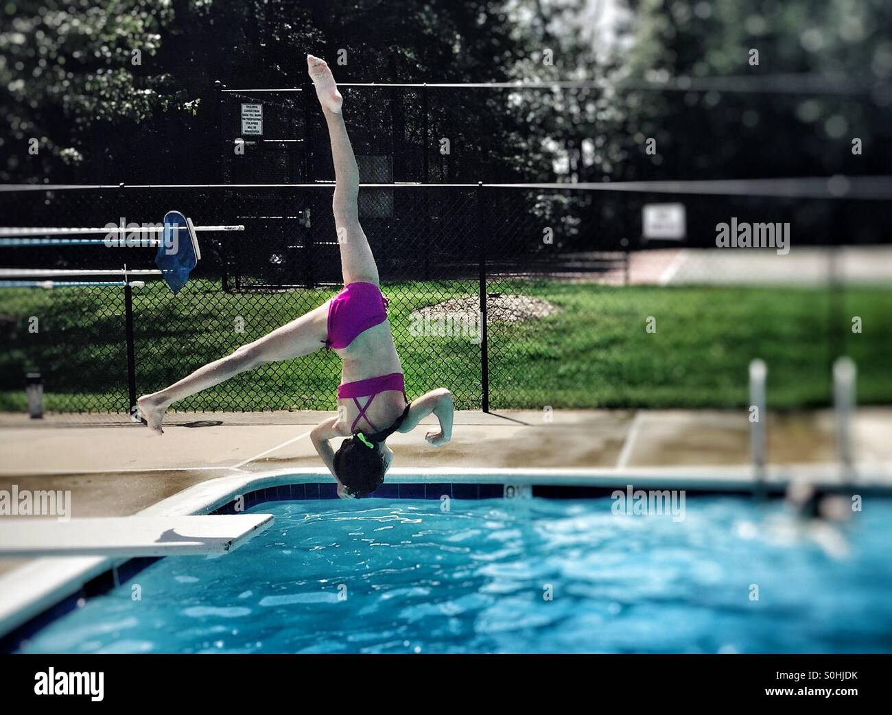 Gymnast girl doing an aerial off a diving board. - Stock Image