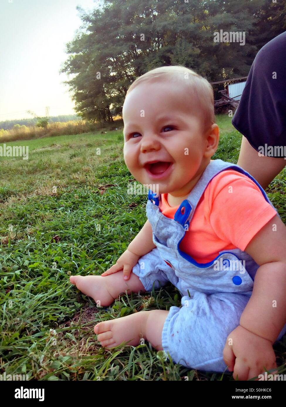 Smiling baby boy sitting on the grass - Stock Image