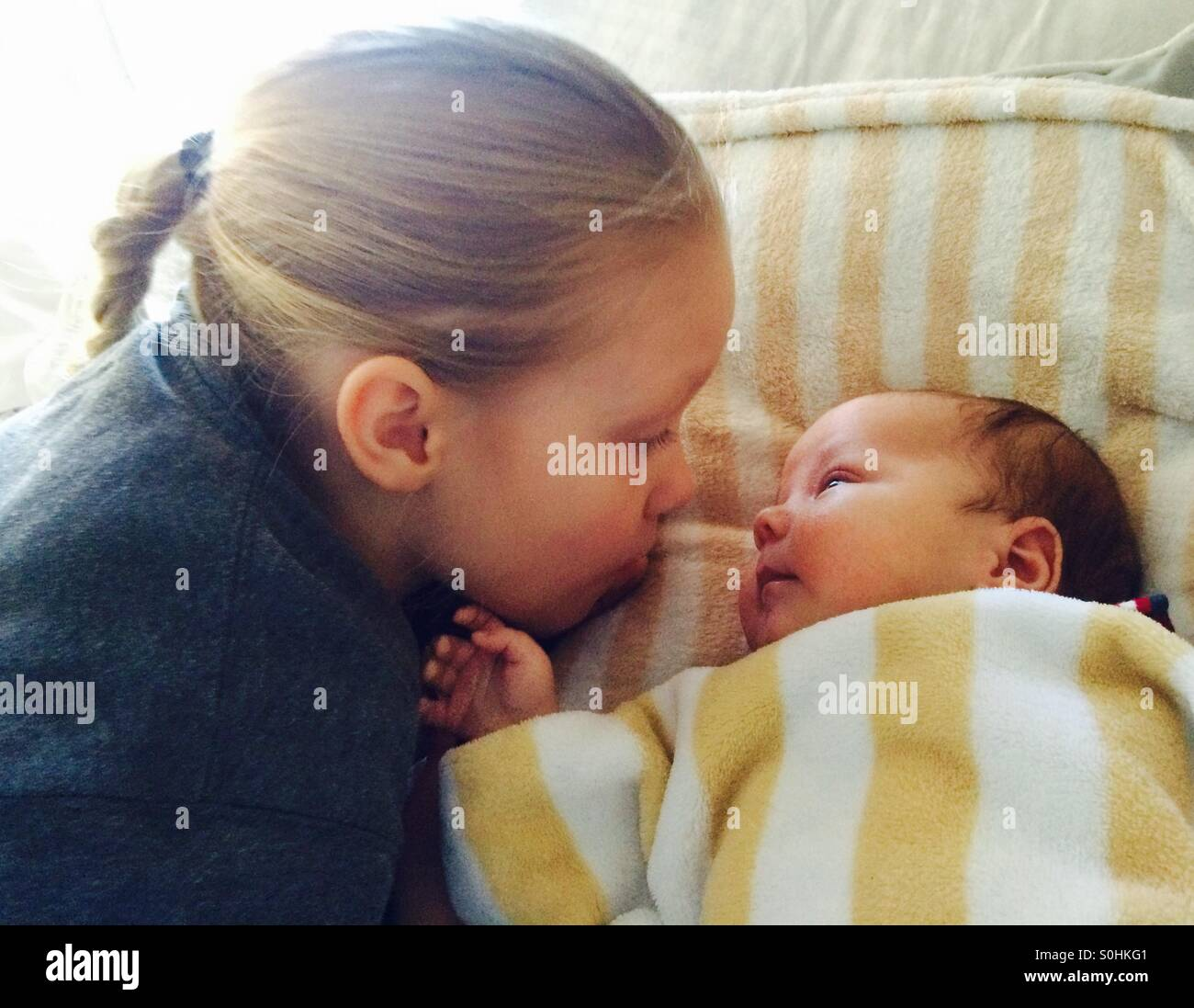 Girl Looking at her baby brother - Stock Image