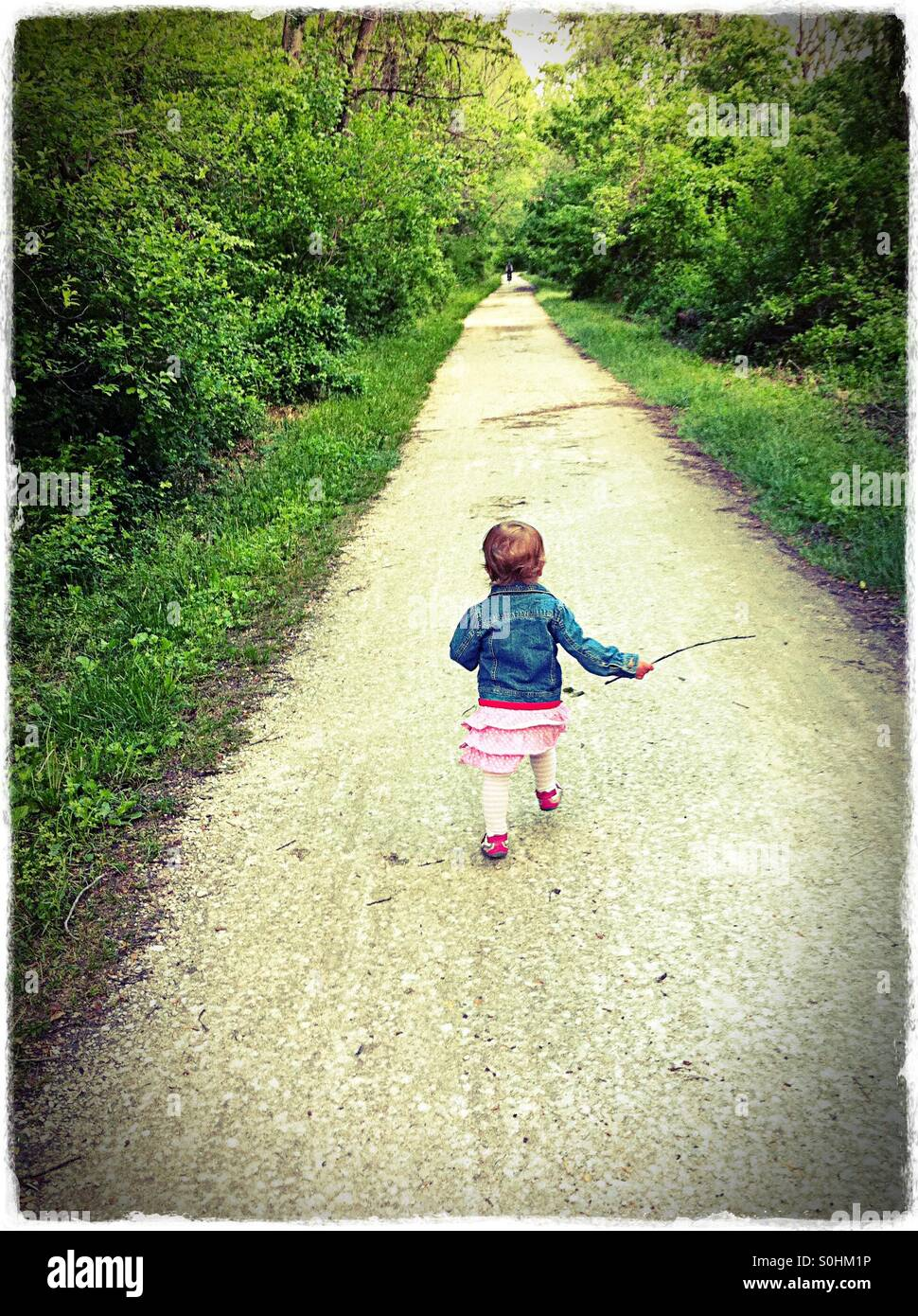 Toddler running down a rail trail in the spring Stock Photo