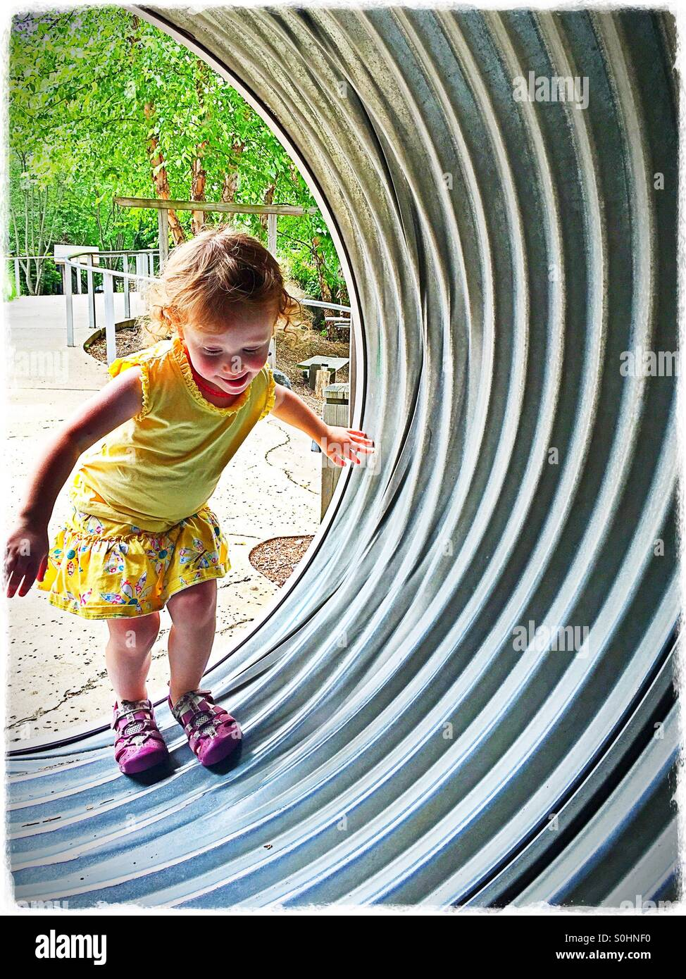 Toddler climbing into tunnel Stock Photo