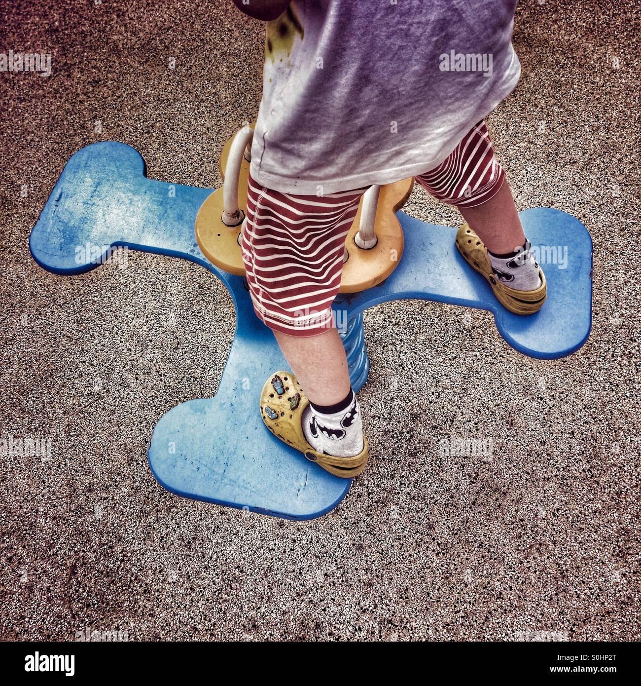Young boy balancing on playground ride - Stock Image