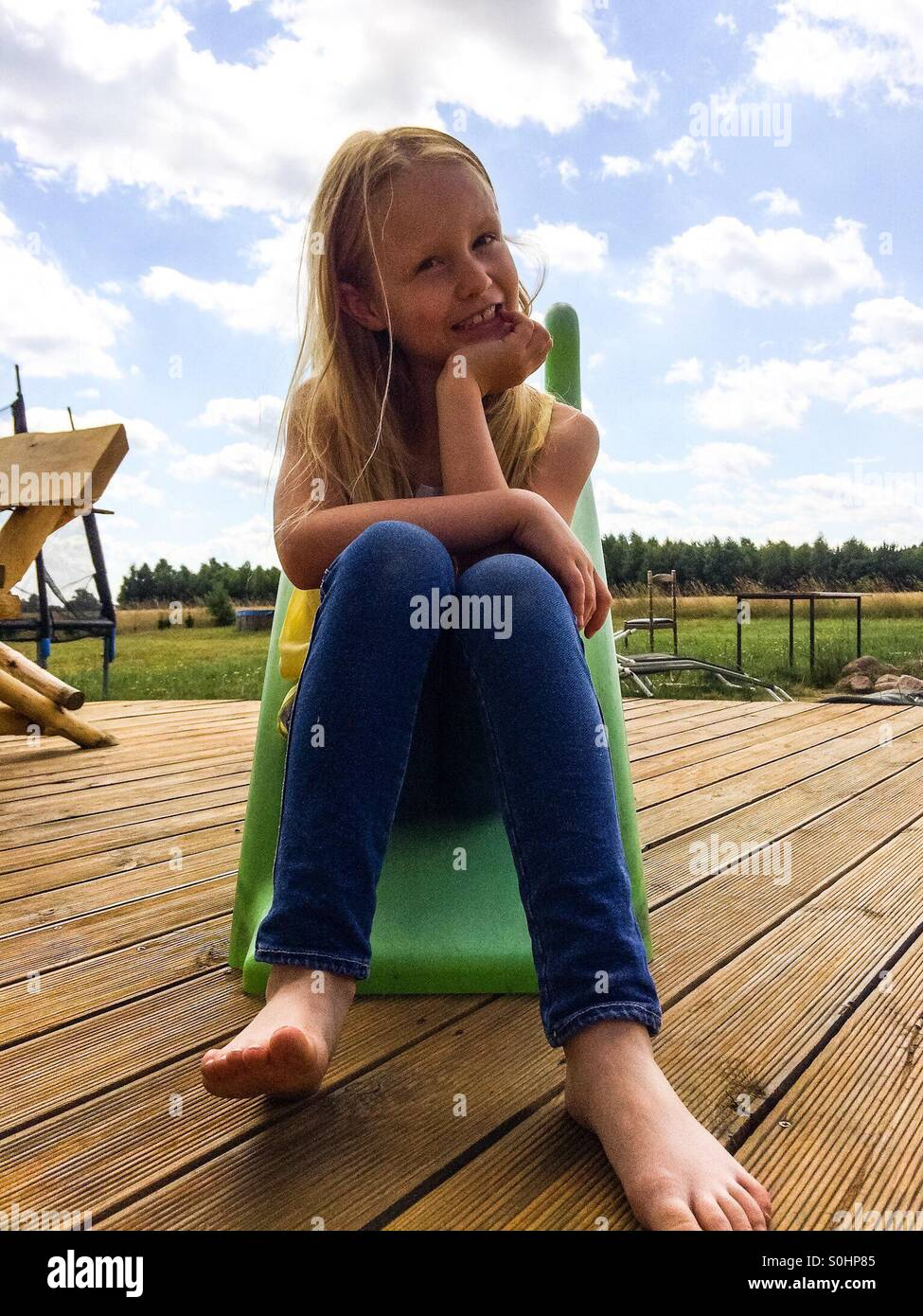 2ea539879d2b2 Girl sitting on a slide on the porch outside Stock Photo  310177285 ...