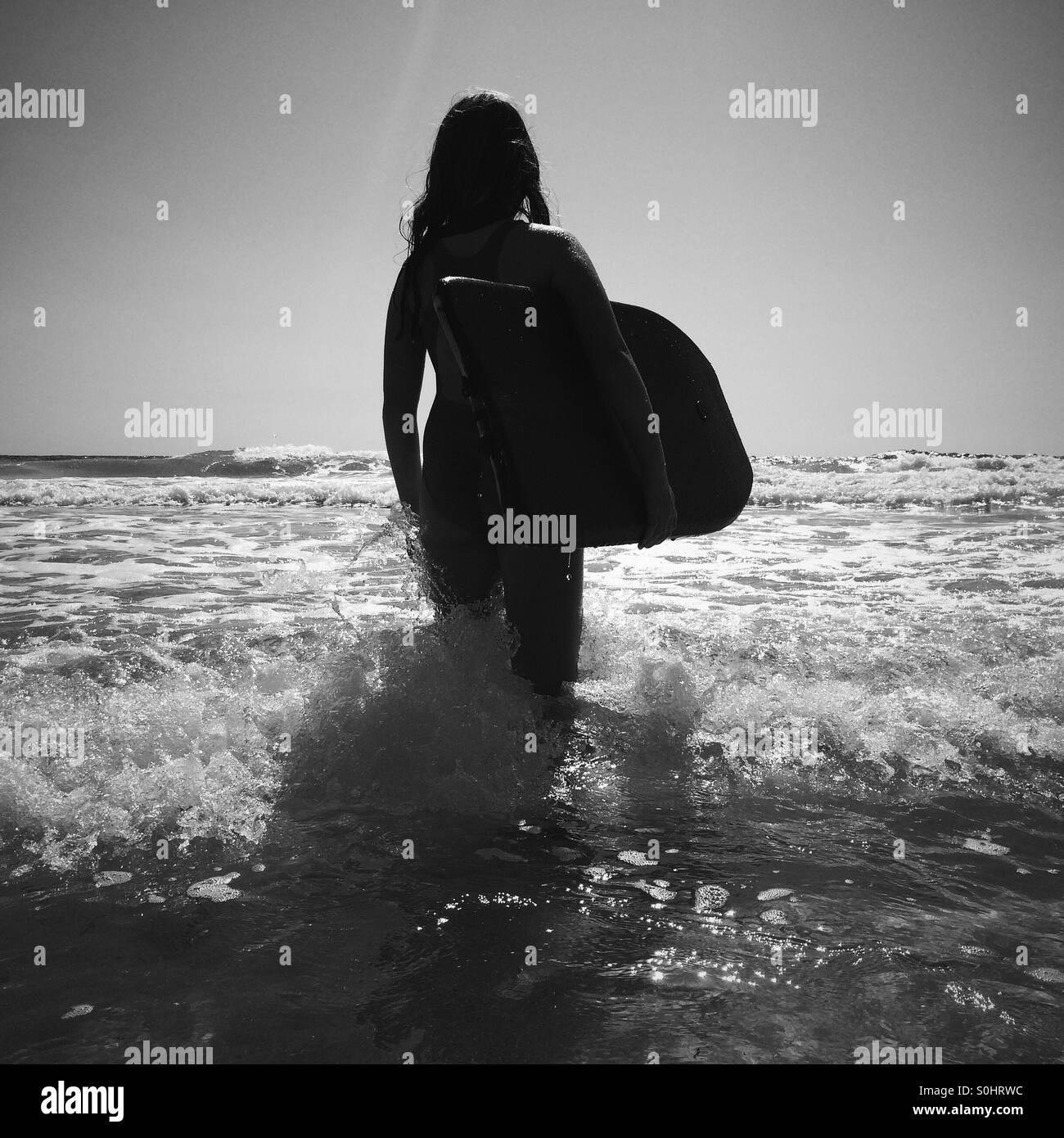 Girl about to go boogie boarding, Falasarna beach, Crete, Greece - Stock Image