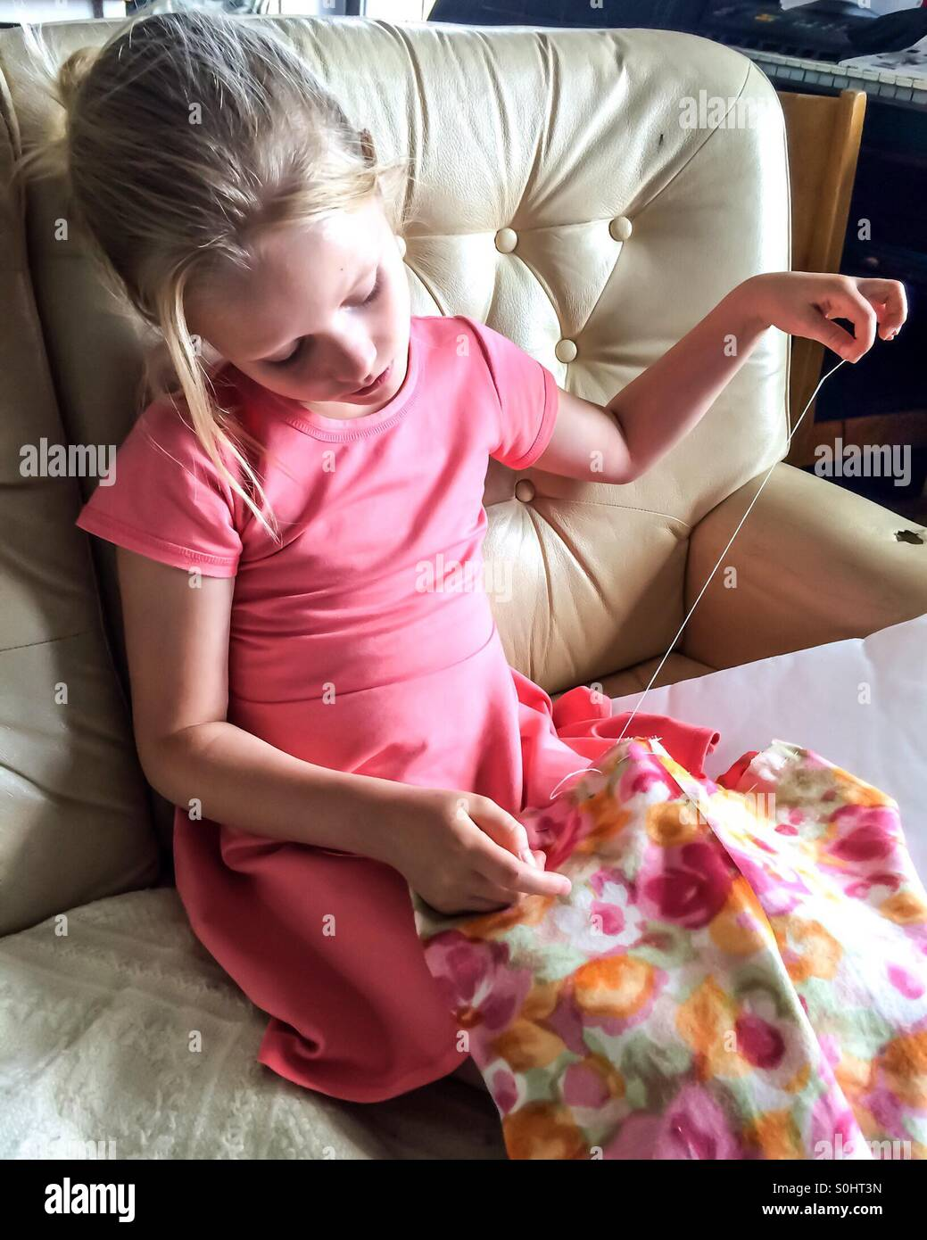 Girl sews a pillow case by hand - Stock Image