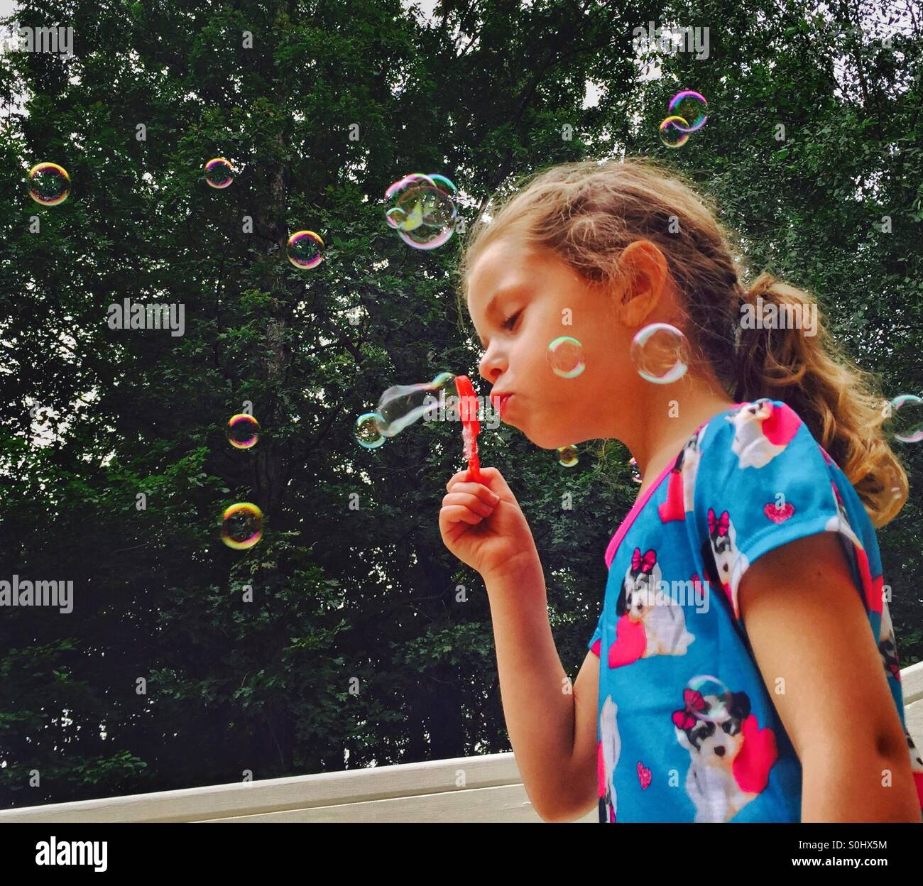 Little girl blowing bubbles - Stock Image