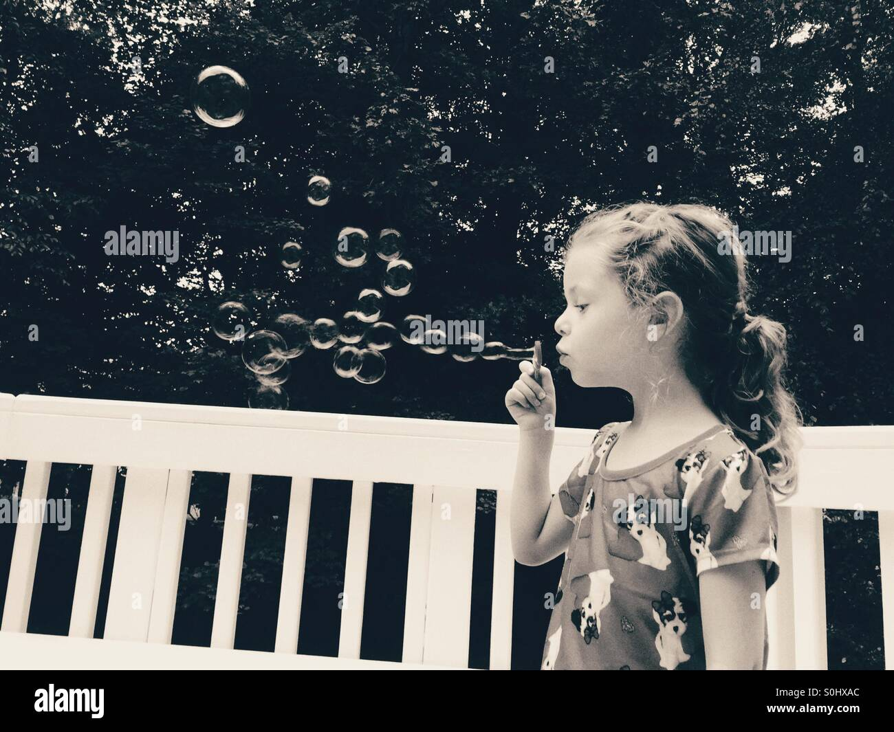 Black and white photo of little girl blowing bubbles outside - Stock Image