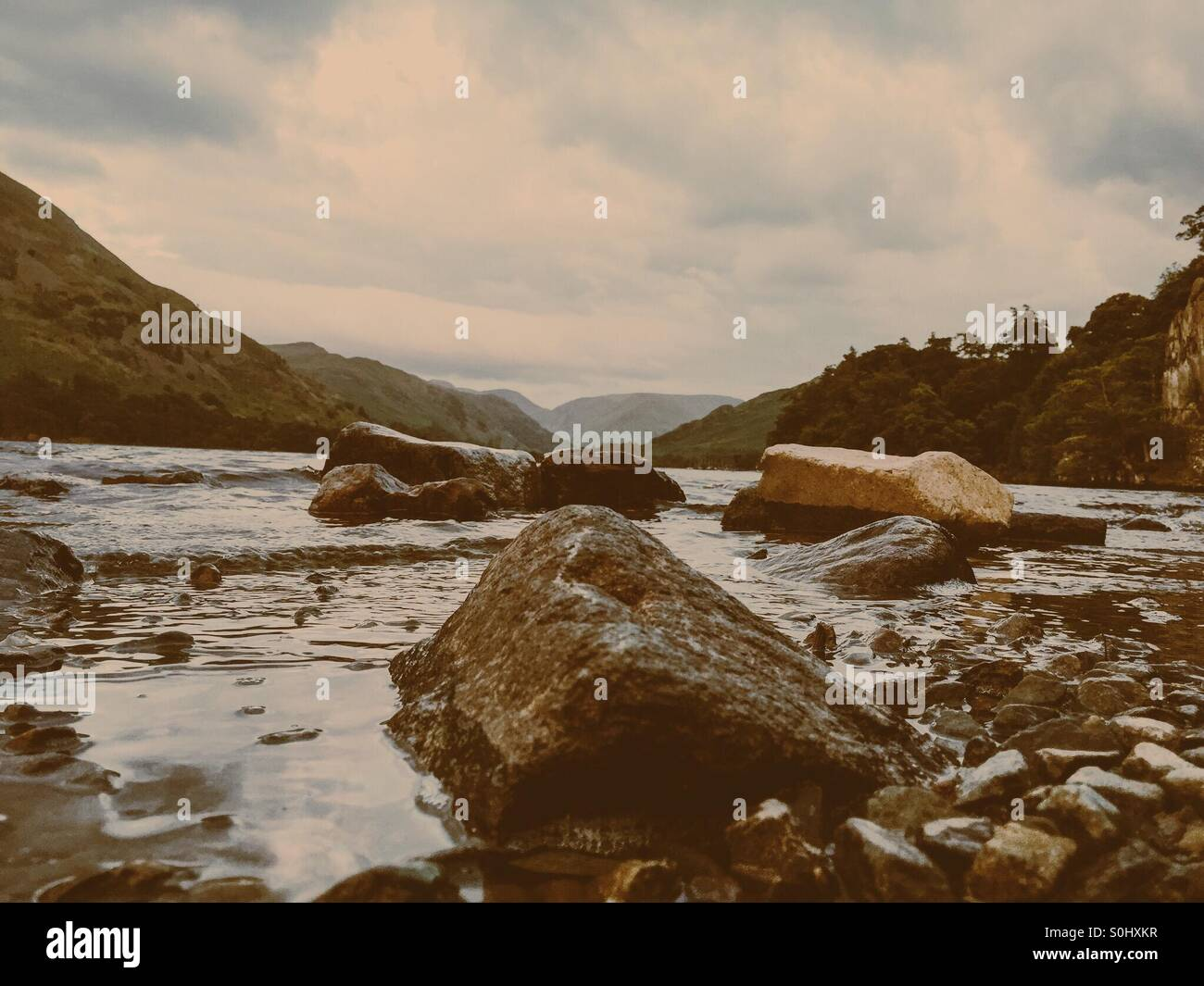 Rocks on the shoreline of Ullswater lake in the late evening light - Stock Image