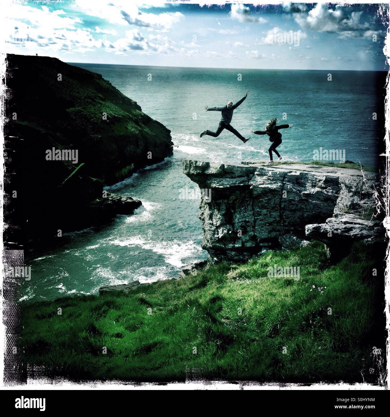 People jump in the air while posing for a photograph on the coastal path in Cornwall, England. - Stock Image