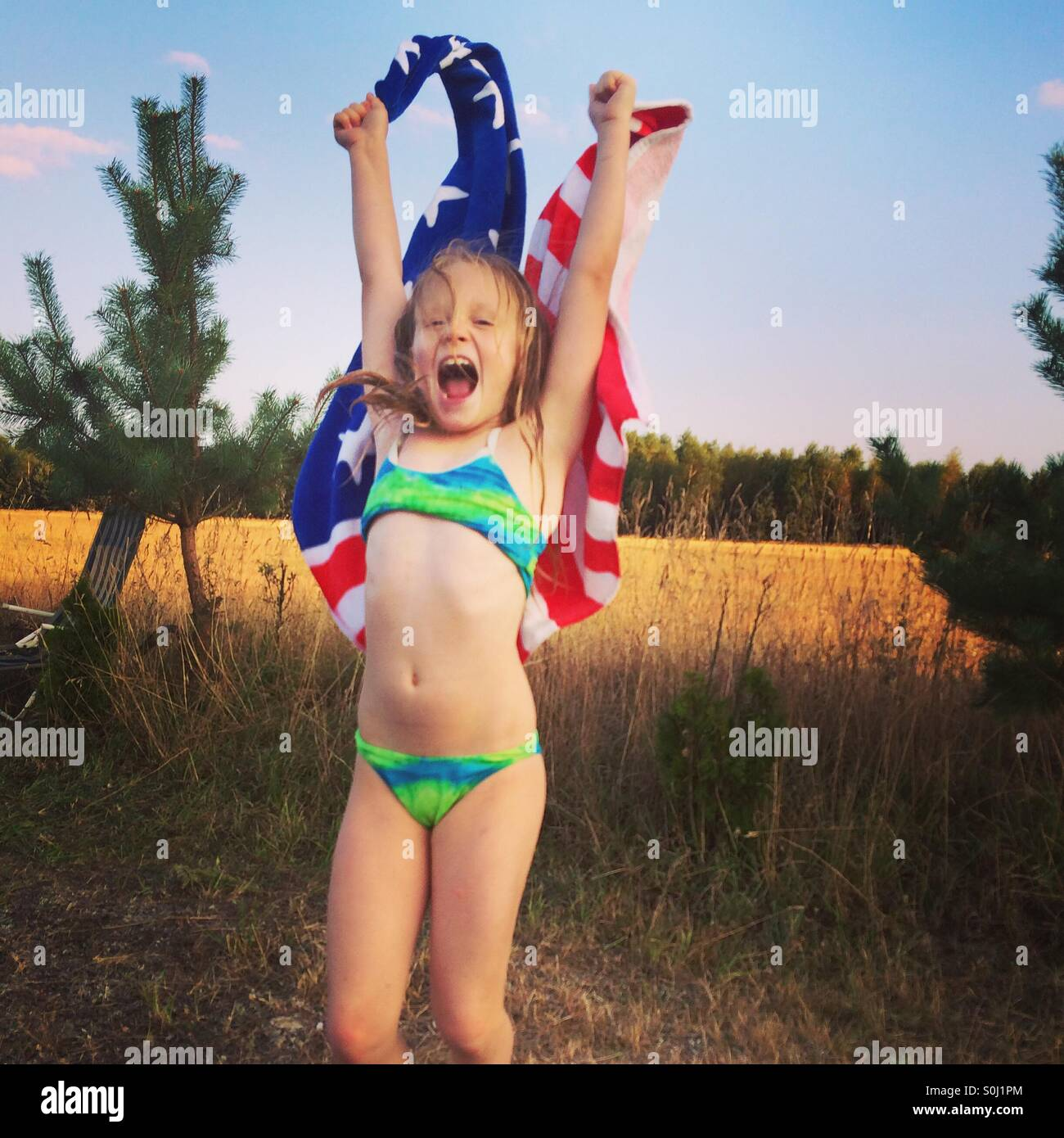 Girl jumping with a flag beach towel - Stock Image