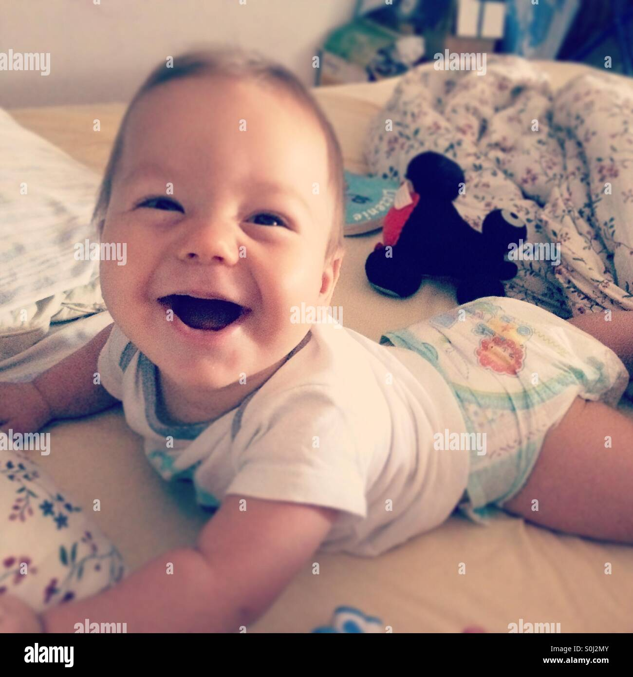 Baby boy smiling lying on his tummy on his parent's bed - Stock Image