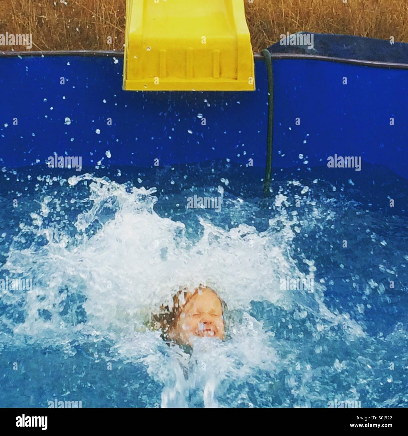 Girl slides down into the water from the diy water slide - Stock Image
