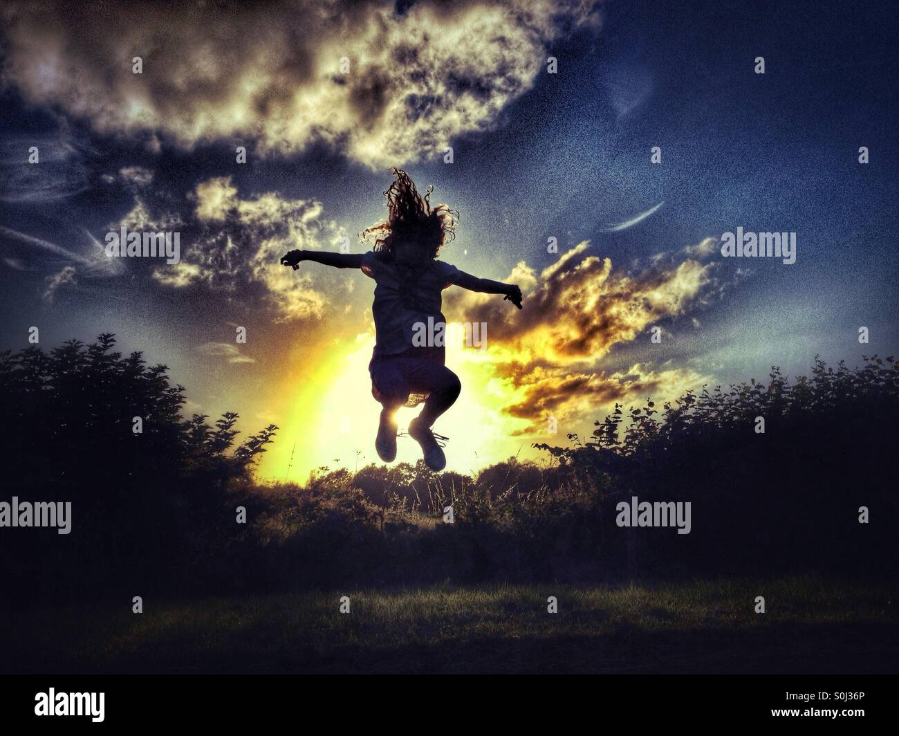 Young girl jumping backlit by late evening sun - Stock Image