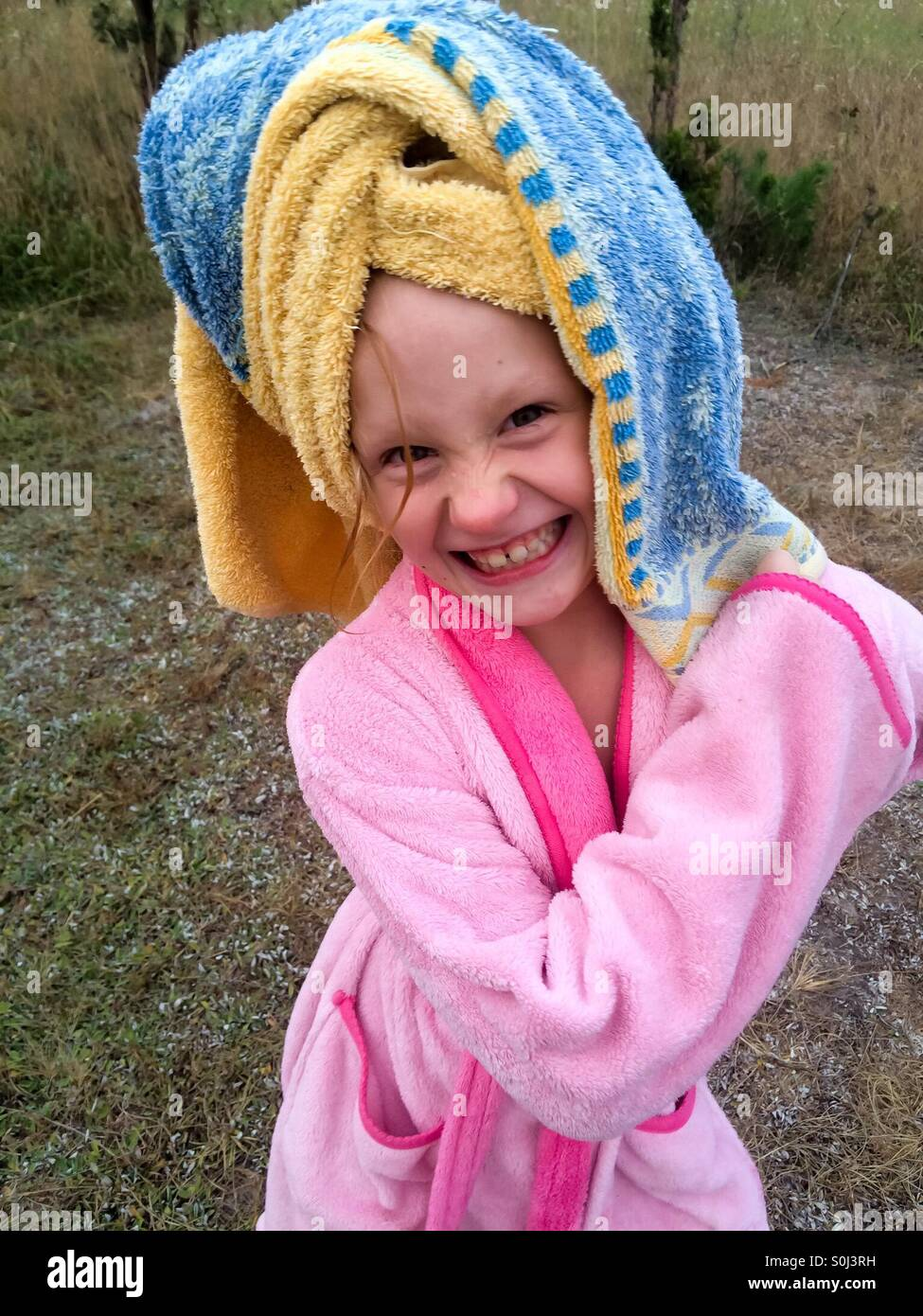 Smiling girl with towel over her wet hair and pink robe, standing outside - Stock Image