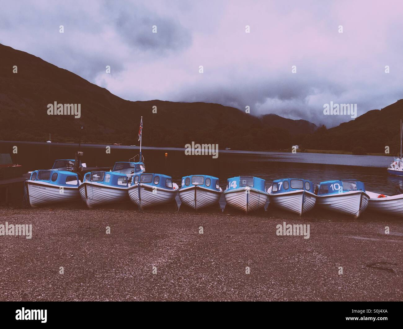 Blue boats all in a row on Ullswater Lake - Stock Image