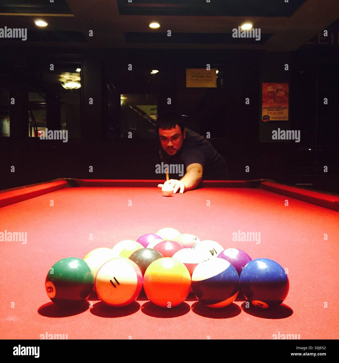 Man prepares to break the rack on a red pool table. - Stock Image