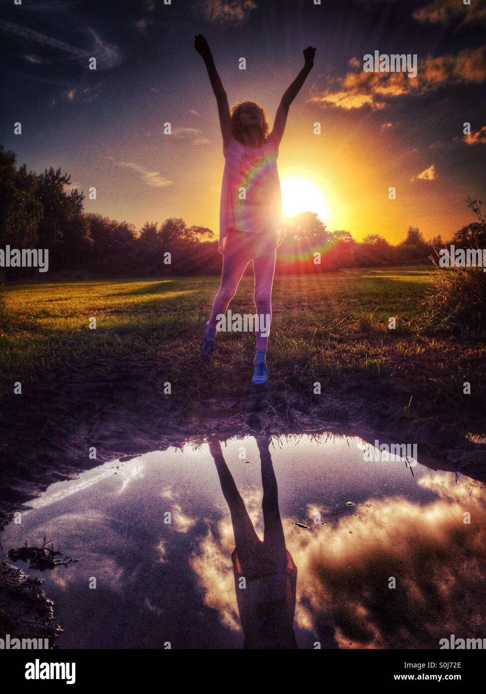 Young girl with arms raised in celebration in front of setting sun - Stock Image