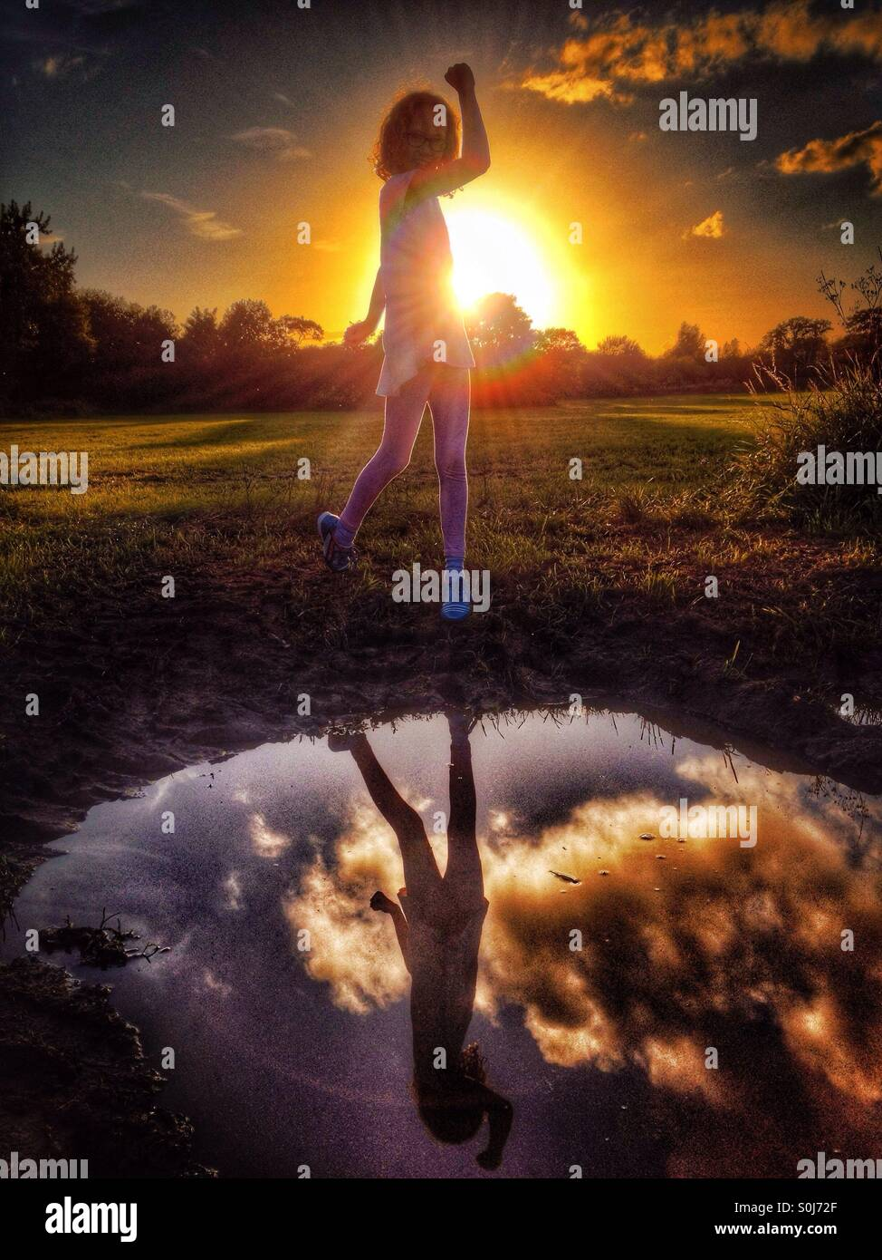 Young girl posing with raised arm in front of setting sun reflected in puddle - Stock Image