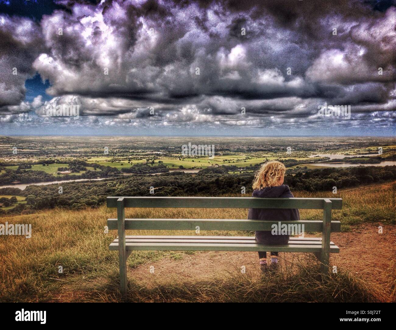 Young girl alone on bench watching approaching storm clouds - Stock Image