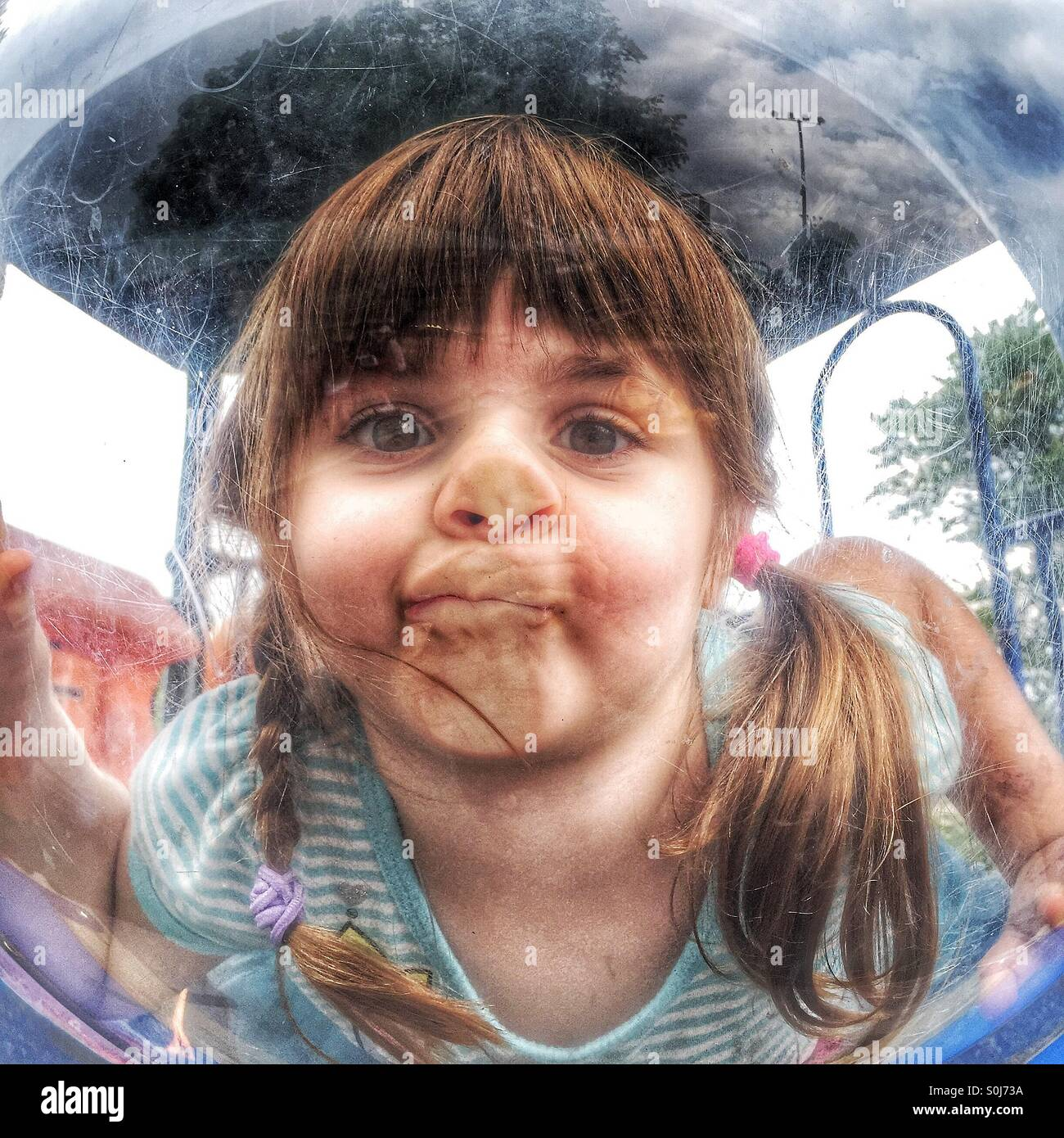 Toddler girl on playground being silly - Stock Image