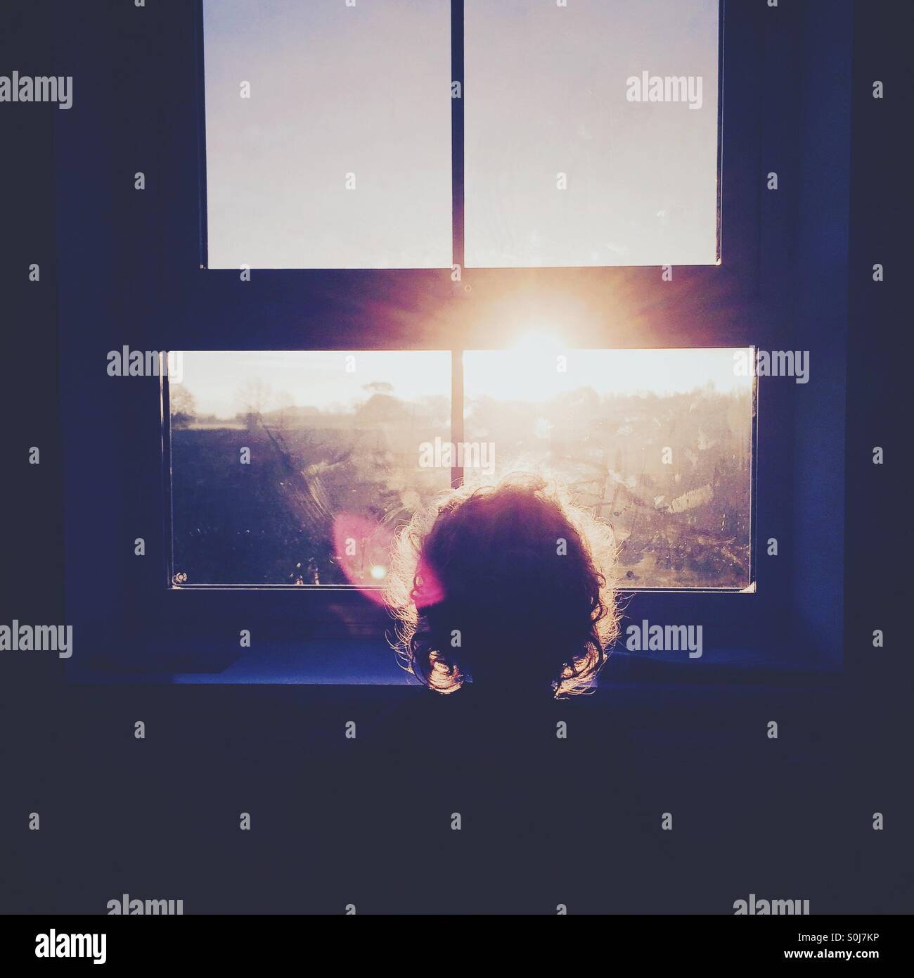 Boy watching sunrise through window - Stock Image