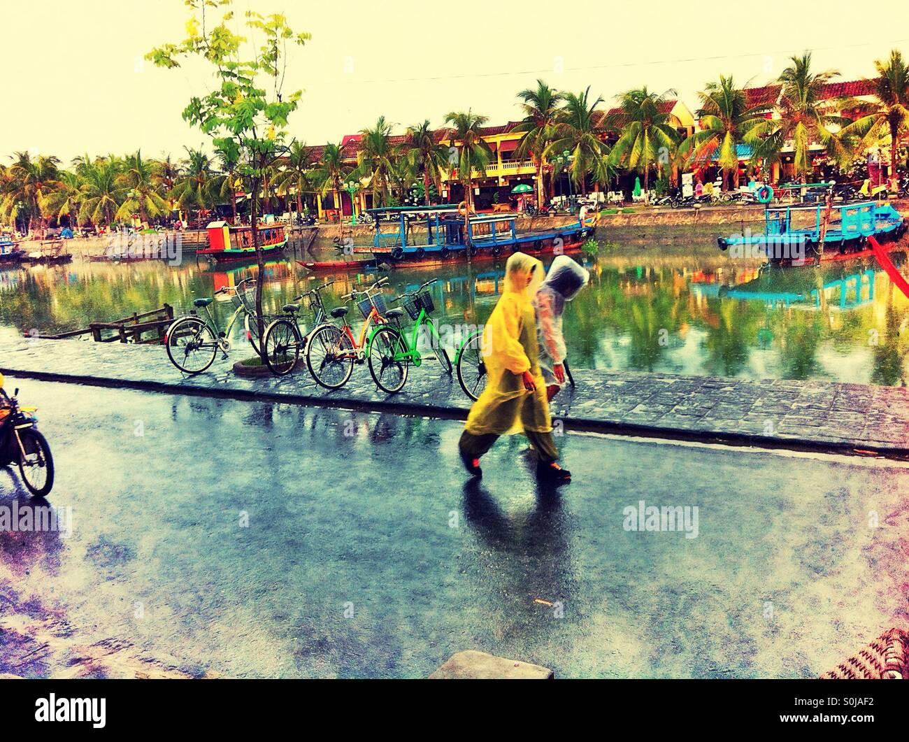 Two people wearing waterproof ponchos walking along Hoi An waterfront, Vietnam - Stock Image