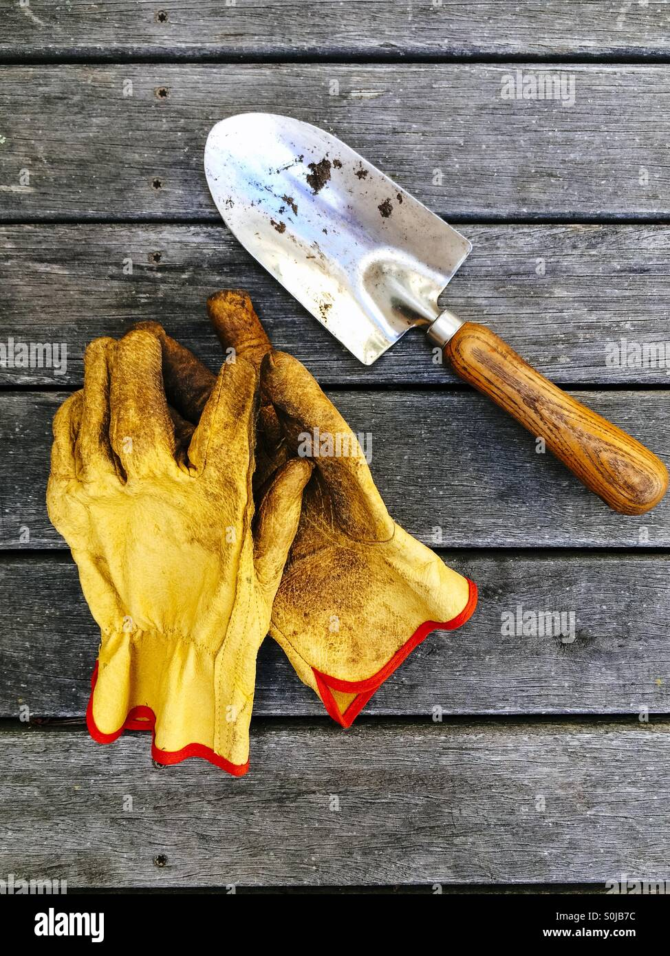 Gardening gloves and hand trowel on wooden deck - Stock Image