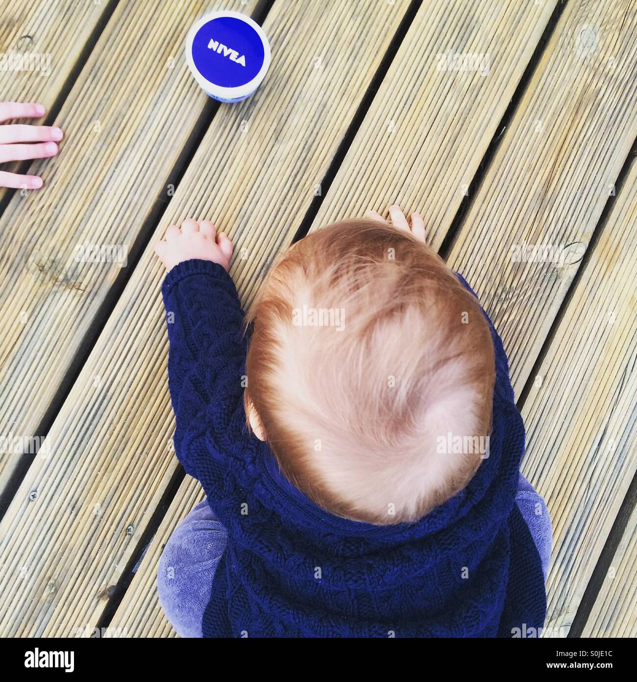 Photo from above  of a baby boy sitting on a wooden deck,  trying to reach the nivea cream - Stock Image