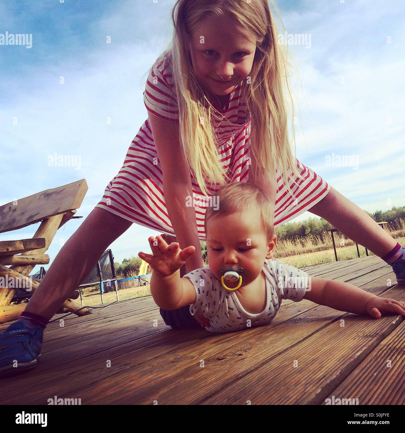 A blonde dressed in a red and white striped dress girl watching over and holding her baby brother who is learning - Stock Image