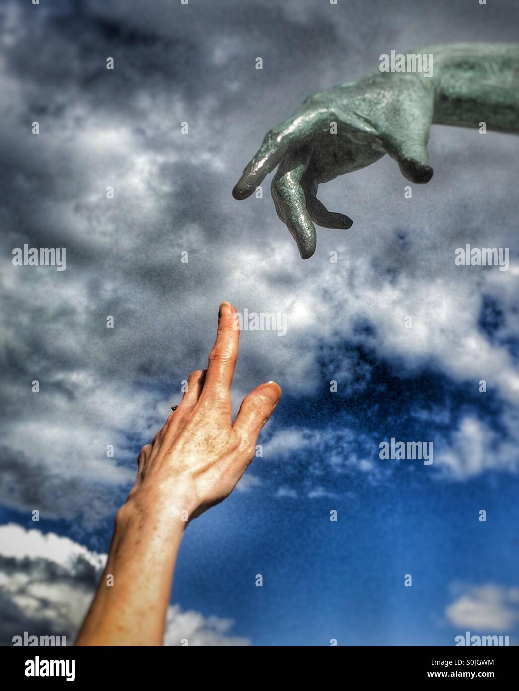 Reaching out touching hands - Stock Image