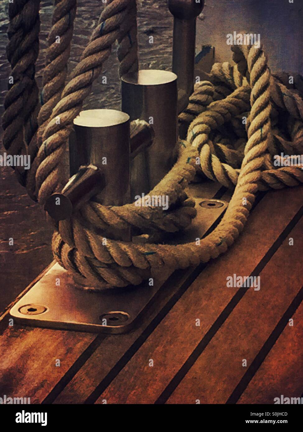 Cleats and rope on the wooden deck - Stock Image