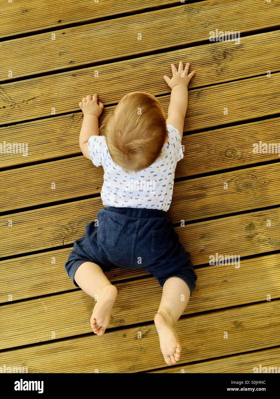 A view from the top of 8 month old baby boy trying to crawl on a wooden deck , outside at the backyard on a warm - Stock Image